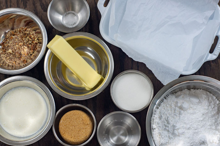 Ingredients for butter-pecan fudge in stainless steel bowls on a wooden surface