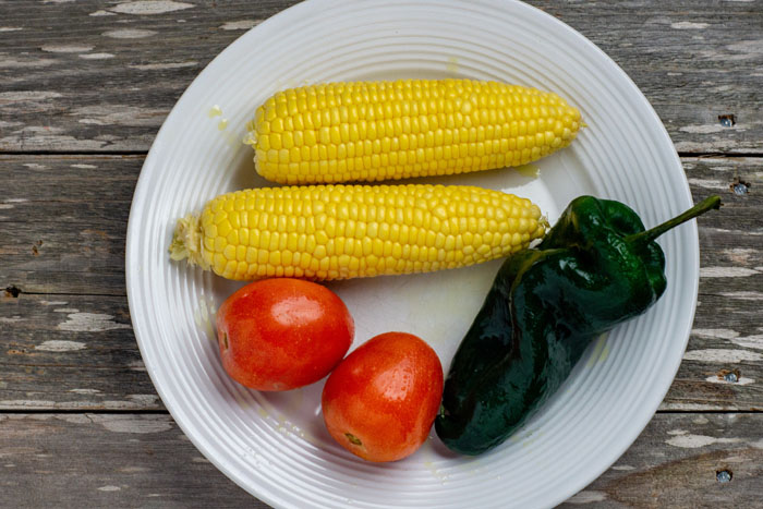 2 cobs of corn, a poblano pepper, and 2 tomatoes covered in oil on a round white plate on a wooden surface