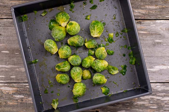 Brussels sprouts covered in oil and seasonings in a square metal baking dish on a wooden surface