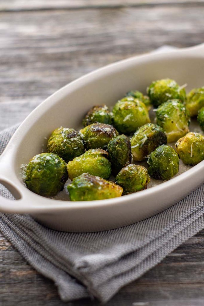 Garlic-Parmesan Brussels Sprouts in a white oval dish on top of a grey napkin on a wooden surface