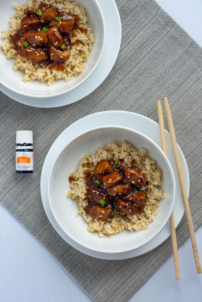 Orange chicken garnished with sesame seeds and sliced green onion on a bed of rice in a round white bowl on top of a round white plate with wooden chopsticks next to a bottle of orange essential oil and another plate of orange chicken on a grey placemat on a white surface (vertical)