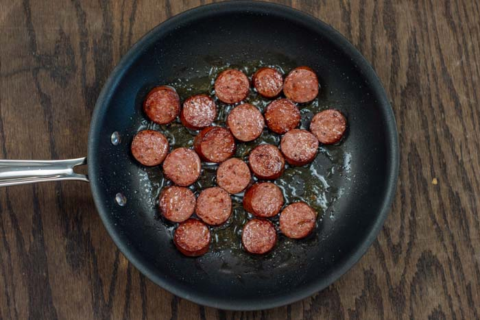 Sausage pieces frying in a skillet on a wooden surface
