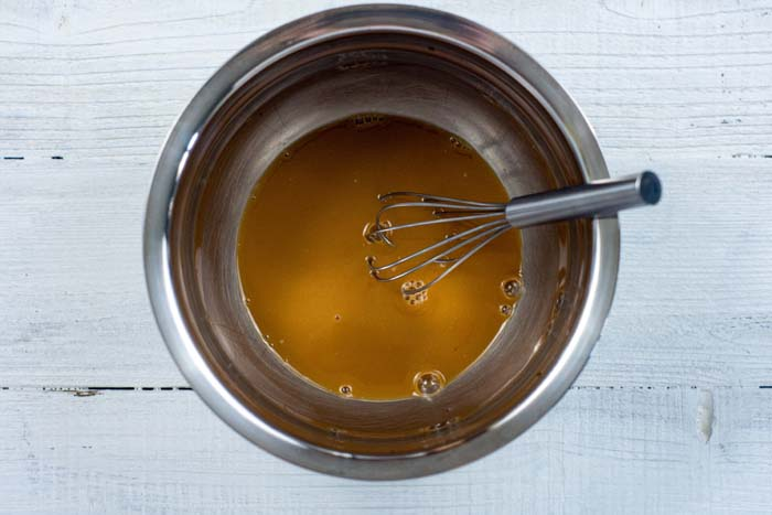 Sweet and sour sauce with a wire whisk in a stainless steel mixing bowl on a white surface