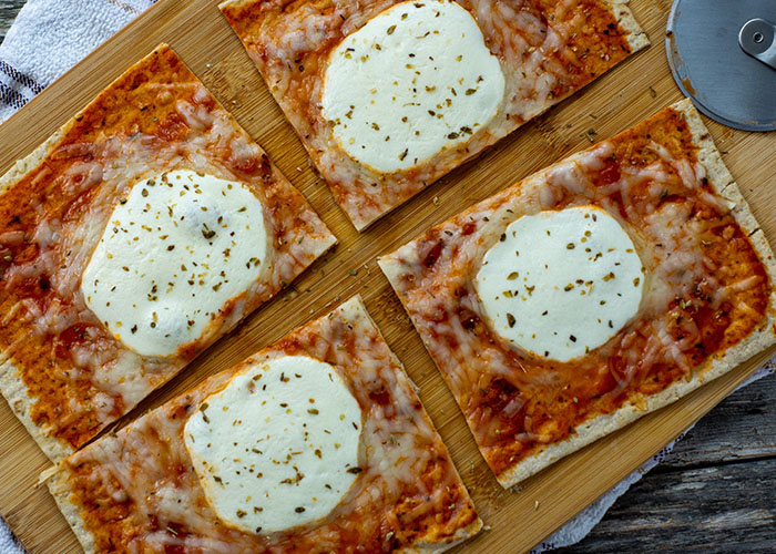 Super Easy Pizza Flatbread on a bamboo tray on top of a white and brown towel on a wooden surface