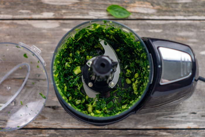 Basil and garlic in a food processor on a wooden surface