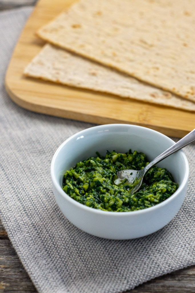 Thai Basil Pesto in a round white bowl with a stainless steel spoon next to a bamboo board with flatbread all on a grey placemat on a wooden surface