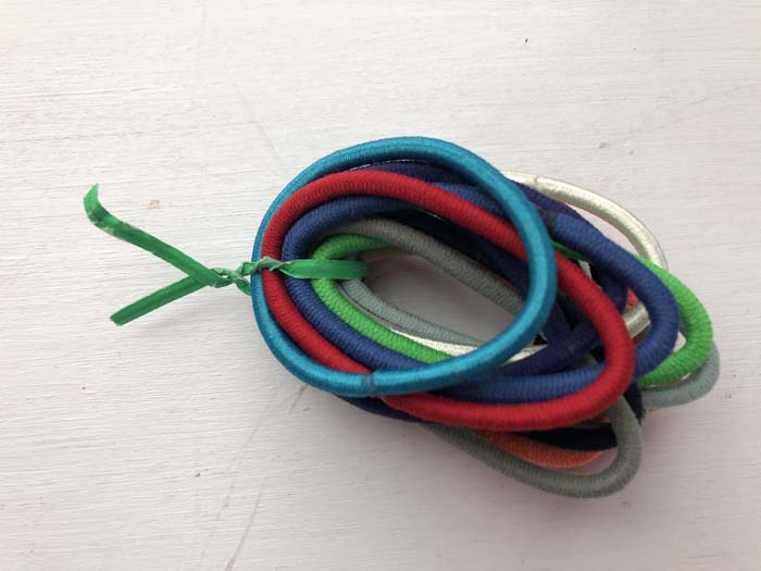 Green twist-tie holding multi-colored hair ties together on a white surface