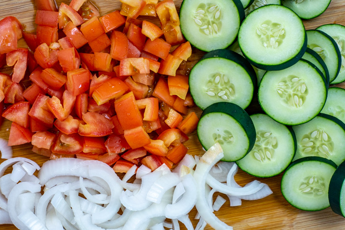 Close-up of diced tomatoes, sliced cucumbers, and sliced onions on a bamboo cutting board