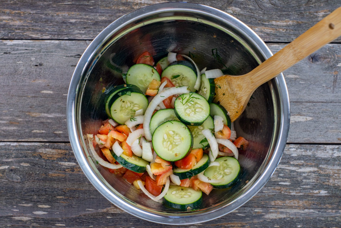 Diced tomatoes, sliced cucumbers, and sliced onions covered with dressing with a wooden spoon in a stainless steel bowl on a wooden surface