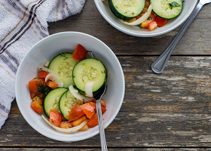 Two white bowls of cucumber summer salad with stainless steel spoons next to a white and brown towel all on a wooden surface