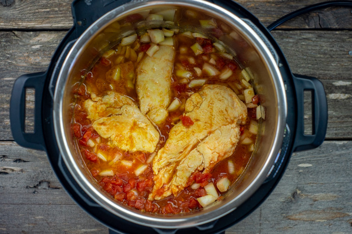 Chicken with sauce and onions in an instant pot on a wooden surface
