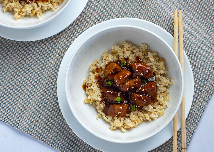 Orange Chicken in the Instant Pot on top of a bed of rice in a round white bowl on a round white plate next to bamboo chopsticks with another serving behind on a grey placemat on a white wooden surface