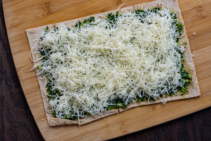 Green pesto spread on a piece of flatbread topped with shredded cheese on a bamboo board on a wooden surface