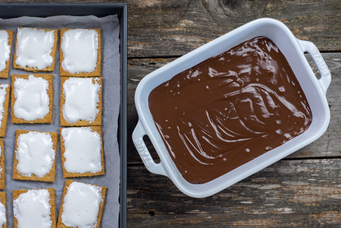 Graham cracker squares topped with marshmallow fluff on a piece of parchment paper on a baking sheet next to melted chocolate in a white casserole dish on a wooden surface