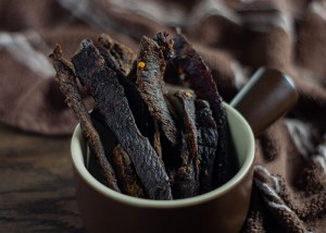 Sticks of beef jerky in a round brown and tan bowl with a brown and white towel behind all on a wooden surface