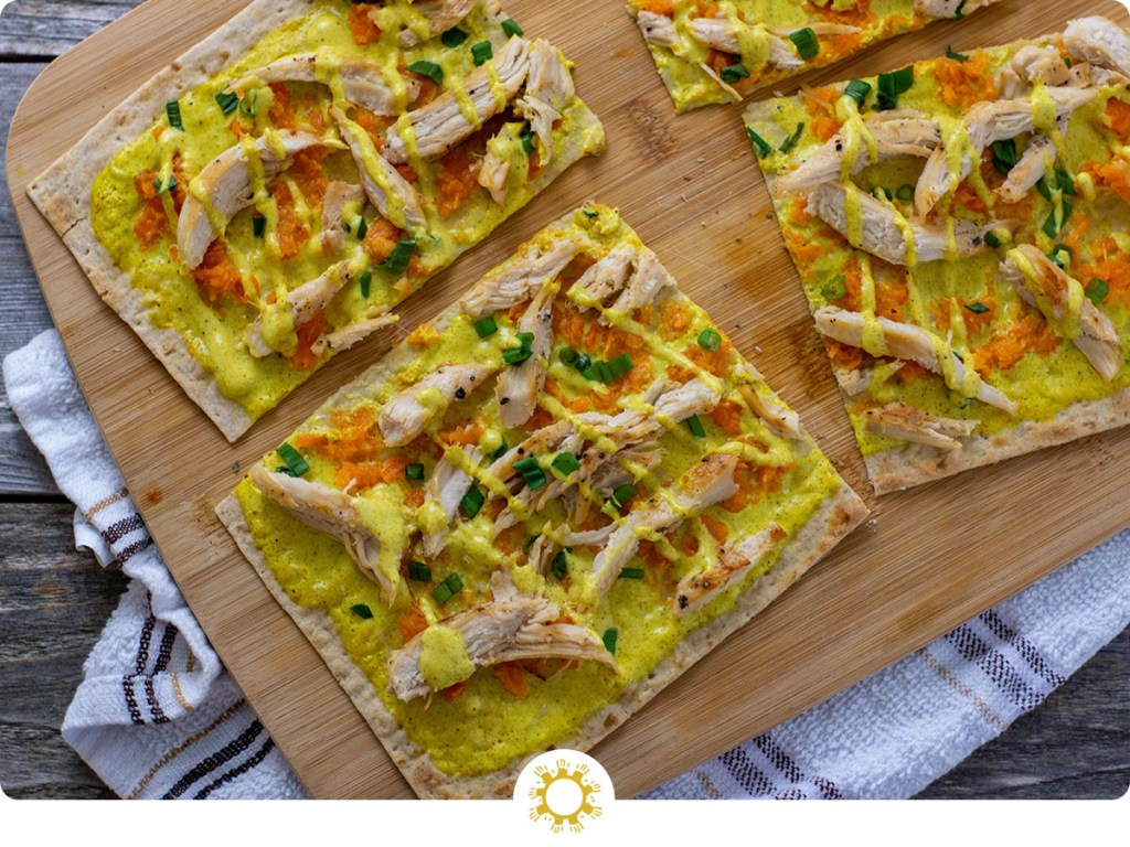 Chicken Curry Flatbread on a bamboo tray on a white and brown towel on a wooden surface (with logo overlay)