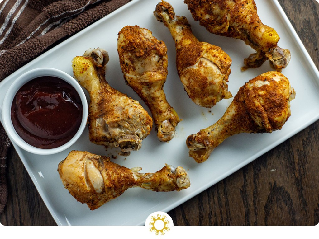 Instant Pot BBQ Chicken Drumsticks on a white rectangular tray with a small round white bowl of bbq sauce all on a wooden surface (with logo overlay)