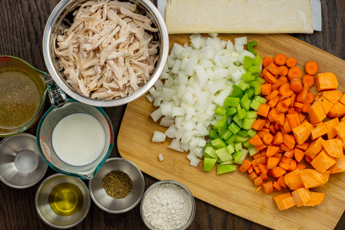 Ingredients for mini chicken pot pies in bowls and on cutting boards on a wooden surface