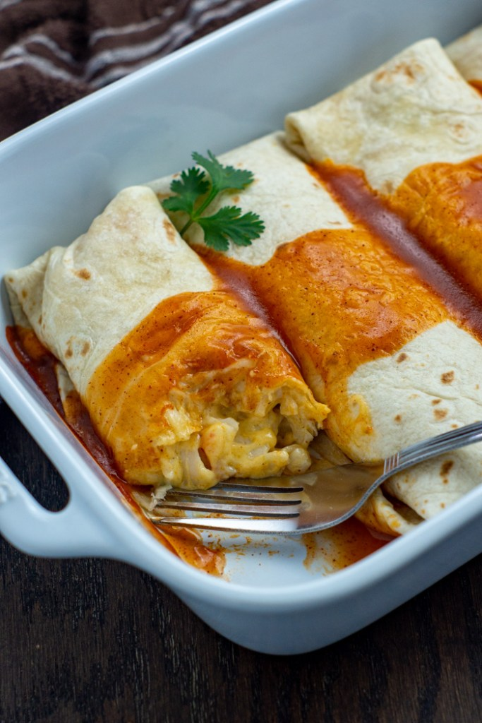 Seafood enchiladas in a white casserole dish with a stainless steel fork on a wooden surface (vertical)
