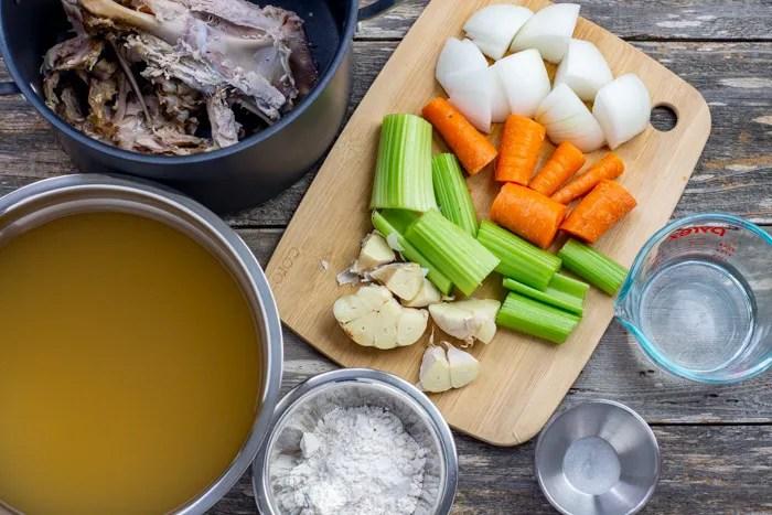 Ingredients for turkey gravy: turkey carcass, chopped vegetables, water, salt, flour, and chicken broth
