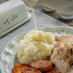 Turkey gravy being poured onto a plate with mashed potatoes, turkey, and candied yams with a butter dish behind on top of a grey placemat on a wooden surface (with title overlay)