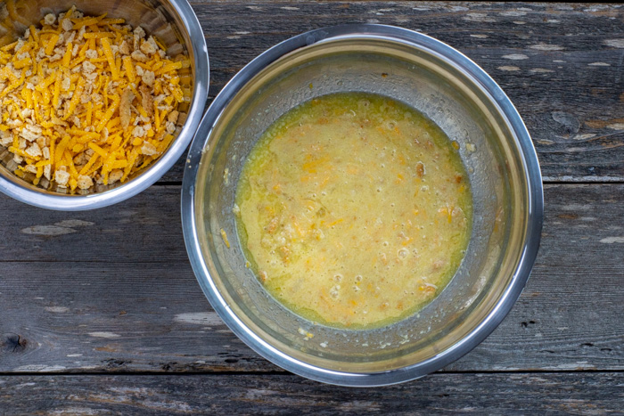 Half of cracker and cheese mixture in a large stainless steel bowl with eggs, milk, and melted butter next to another smaller stainless steel bowl with remaining cracker and cheese mixture all on a wooden surface