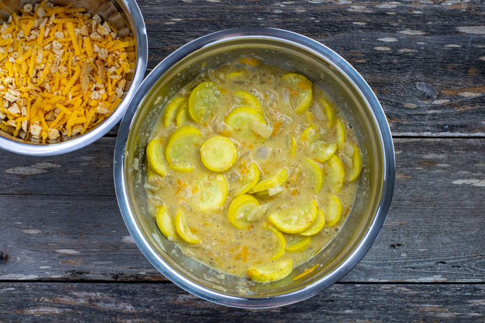 Half of cracker and cheese mixture in a large stainless steel bowl with eggs, milk, and melted butter mixed with cooked onions, garlic, and yellow squash next to another smaller stainless steel bowl with remaining cracker and cheese mixture all on a wooden surface