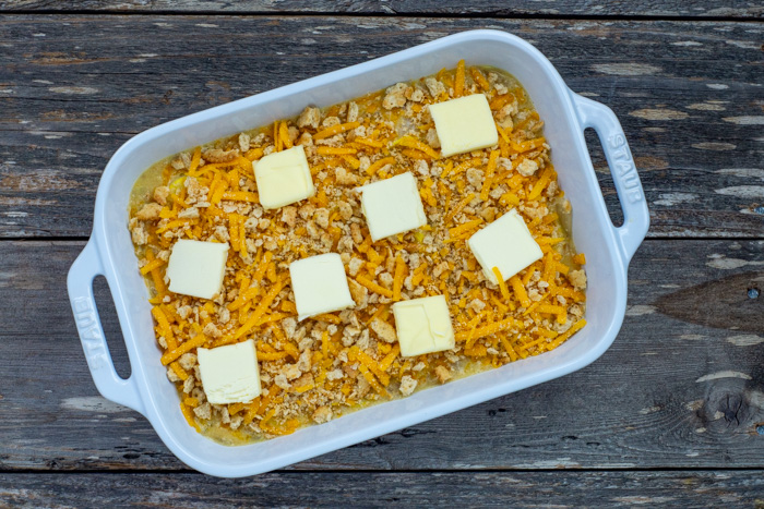 Yellow squash mixture covered with remaining cracker and cheese mixture and topped with slices of butter in a white rectangular casserole dish on a wooden surface