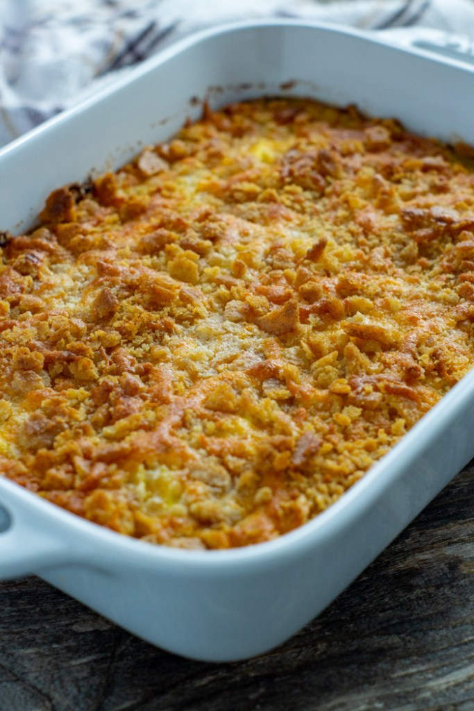 Cooked yellow squash casserole in a white rectangular casserole dish with a white and brown towel behind all on a wooden surface (vertical)