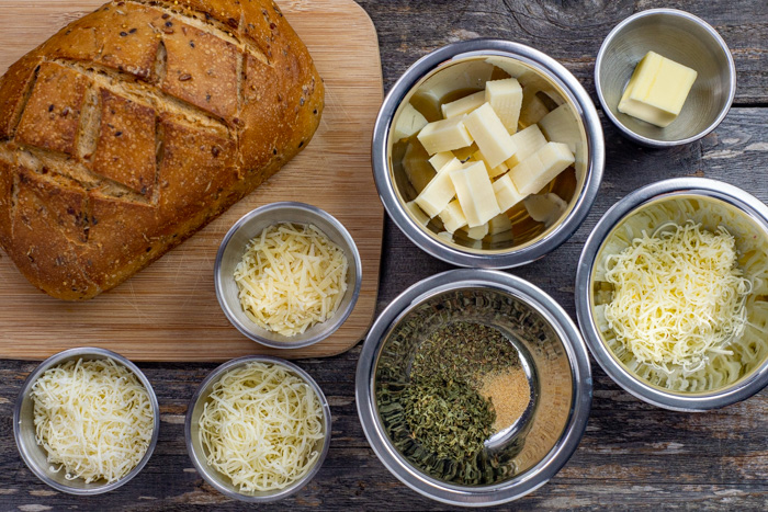 Ingredients for five cheese pull-apart bread in stainless steel bowls on a wooden surface