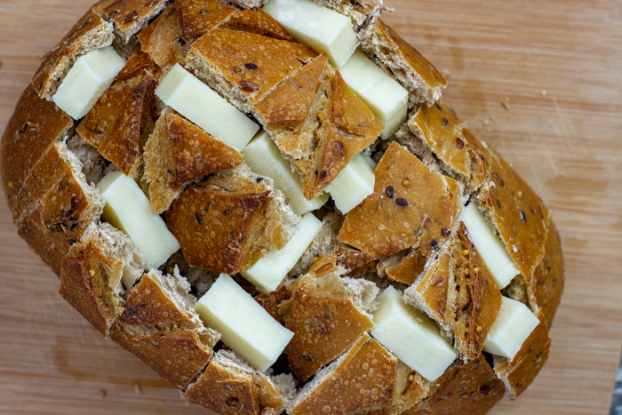 Artisan bread with chunks of mozzarella cheese stuffed into horizontal and vertical slices all on a bamboo board