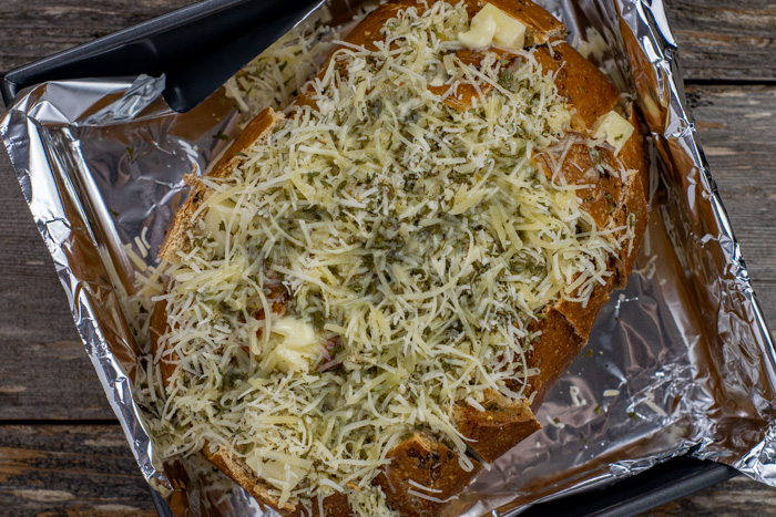 Artisan bread with chunks of mozzarella cheese stuffed into horizontal and vertical slices covered with shredded cheeses and seasonings topped with melted butter on a foil-lined baking pan on a wooden surface
