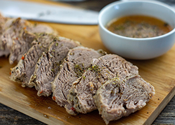 Instant Pot Pork Tenderloin sliced on a bamboo tray with dipping sauce in a round white bowl behind all on a wooden surface