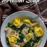 Leftover turkey tortellini soup in a round white bowl next to a brown and white towel on a dark wood surface (with title overlay)