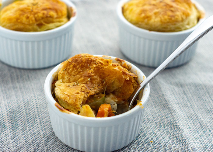 3 mini chicken pot pies in round white ramekins with a stainless steel spoon on a grey cloth surface