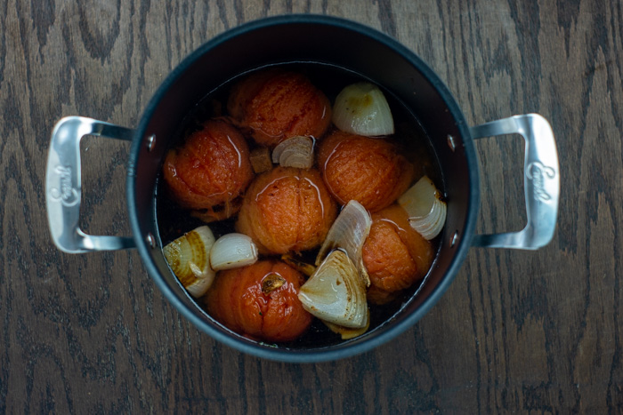 Peeled roasted tomatoes and onions covered with chicken broth in a large stockpot on a wooden surface