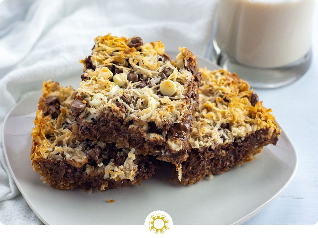 3 Triple Chocolate Coconut Bars on a square white plate on a white towel with a glass of milk behind all on a white wooden surface (with logo overlay)