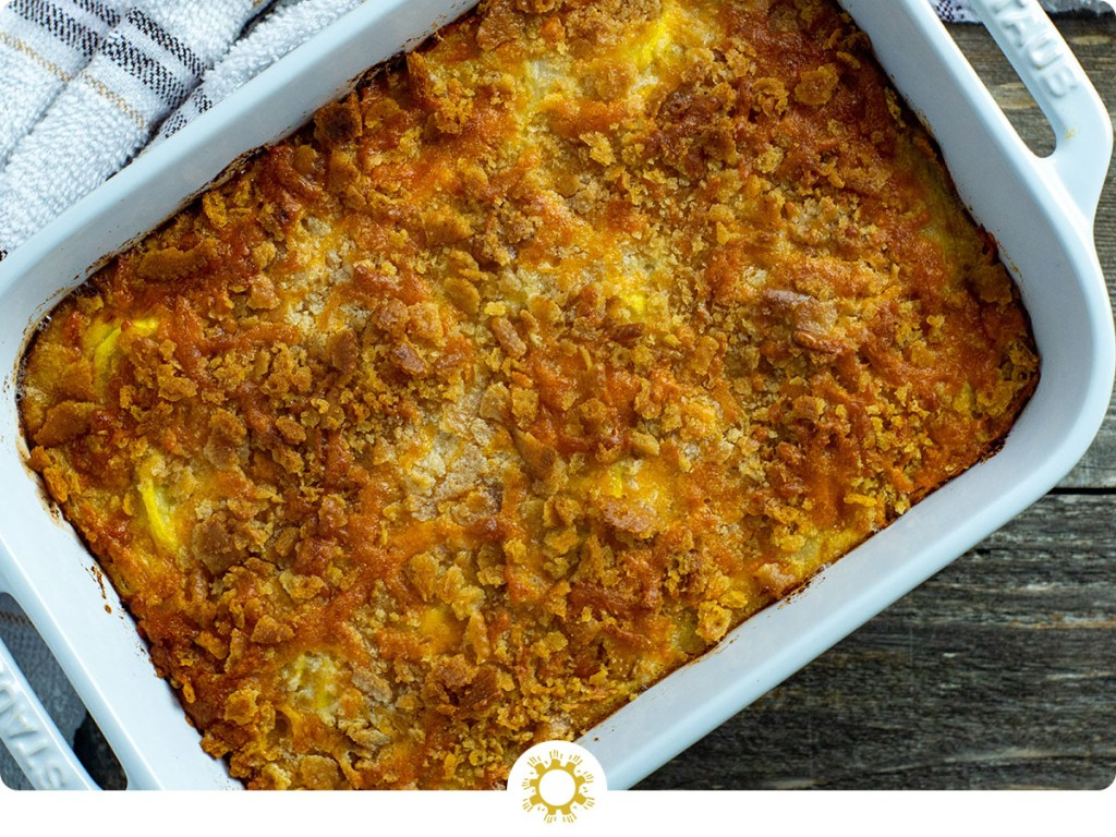 Yellow squash casserole in a white casserole dish with a white and brown towel behind all on a wooden surface (with logo overlay)