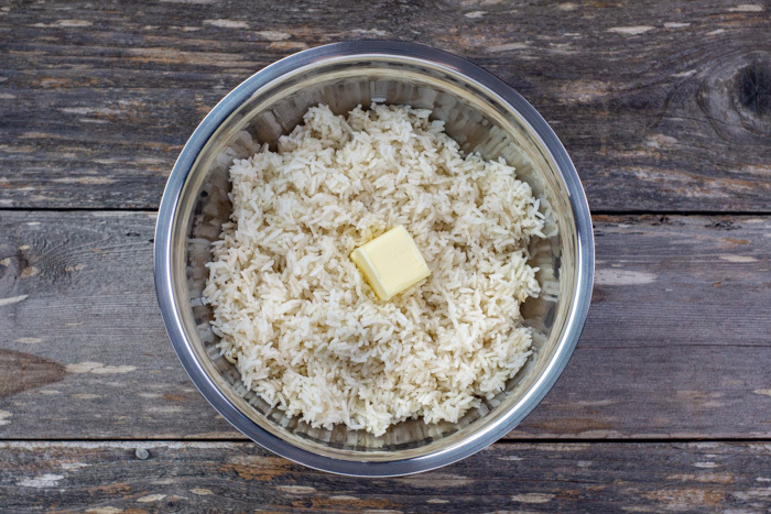 Cooked rice with a square piece of butter in a stainless steel bowl on a wooden surface