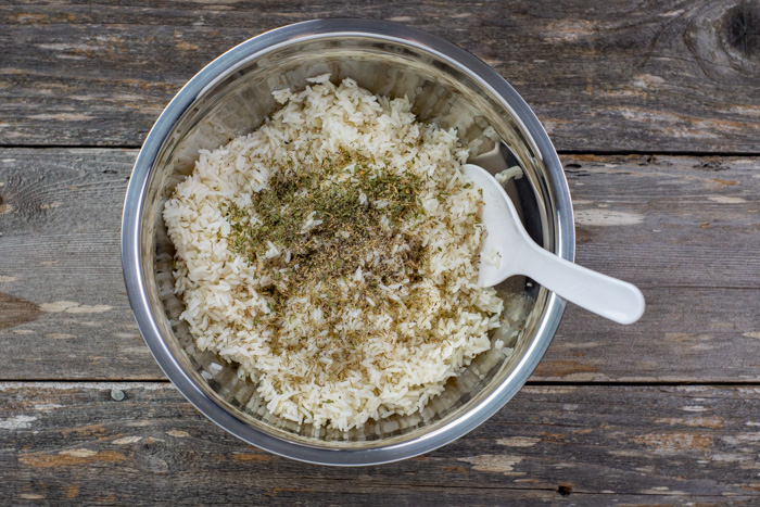 Seasonings on cooked rice with a white rice paddle in a stainless steel bowl on a wooden surface