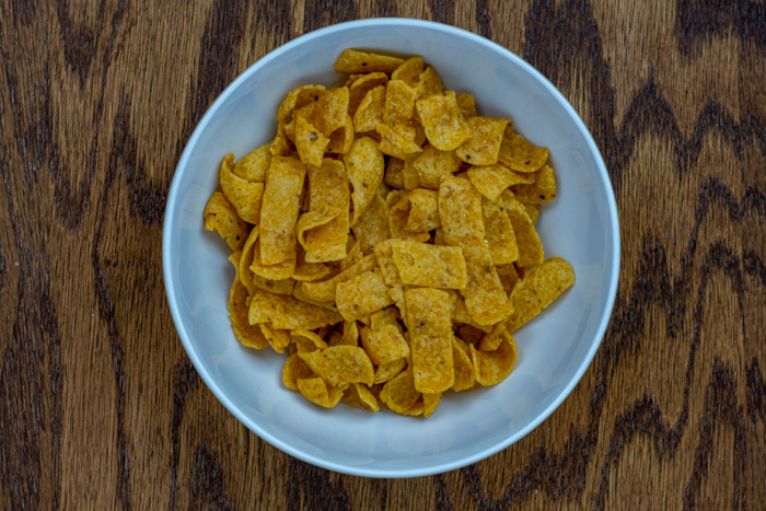 Frito chips in a white bowl on a wooden surface