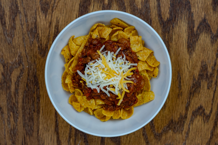 Frito chips, chili, and cheese in a white bowl on a wooden surface