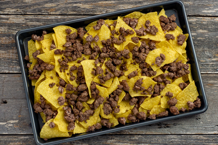 Tortilla chips covered with ground beef on a metal baking sheet on a wooden surface