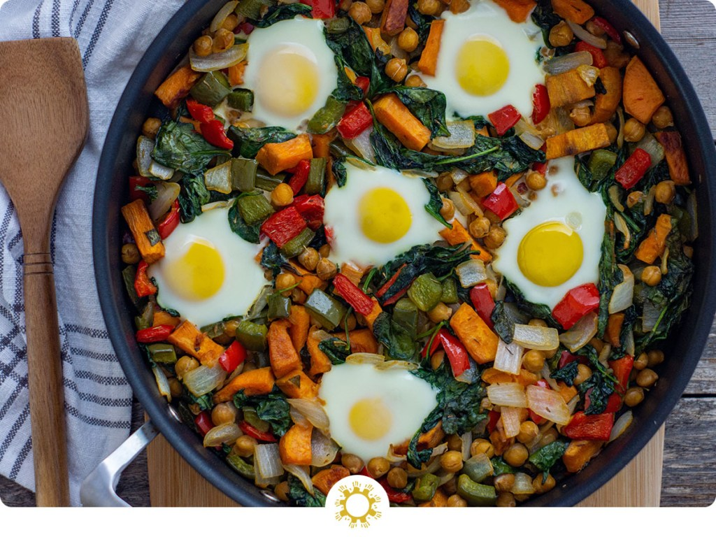 Healthy breakfast hash of sweet potatoes, chickpeas, bell peppers, onion, spinach, and eggs in a skillet on a bamboo cutting board with a white and grey towel behind all on a wooden surface (with logo overlay)