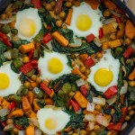 Healthy breakfast hash of sweet potatoes, chickpeas, bell peppers, onion, spinach, and eggs in a skillet on a bamboo cutting board with a white and grey towel behind all on a wooden surface (with title overlay)