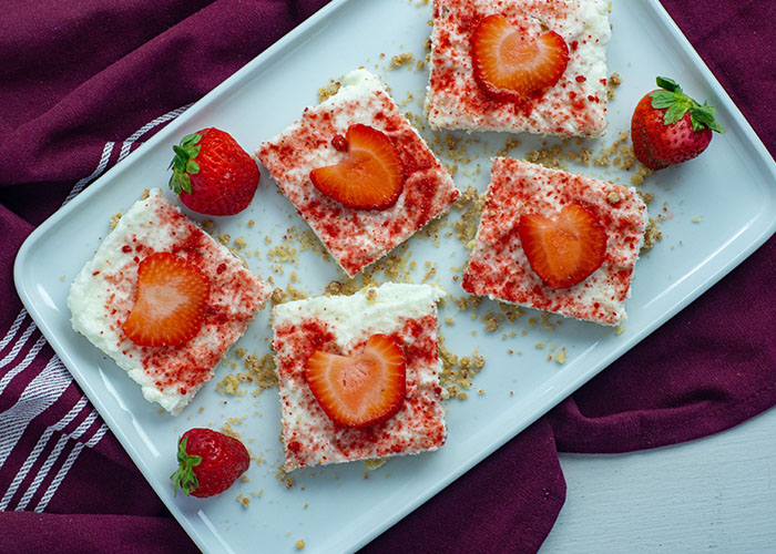 White chocolate strawberry dessert bars with whole strawberries and dried strawberry powder on a long white dish on top of a red and white placemat on a white surface