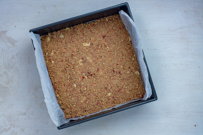 Cracker and strawberry crust pressed into a parchment-lined metal baking pan on a white surface