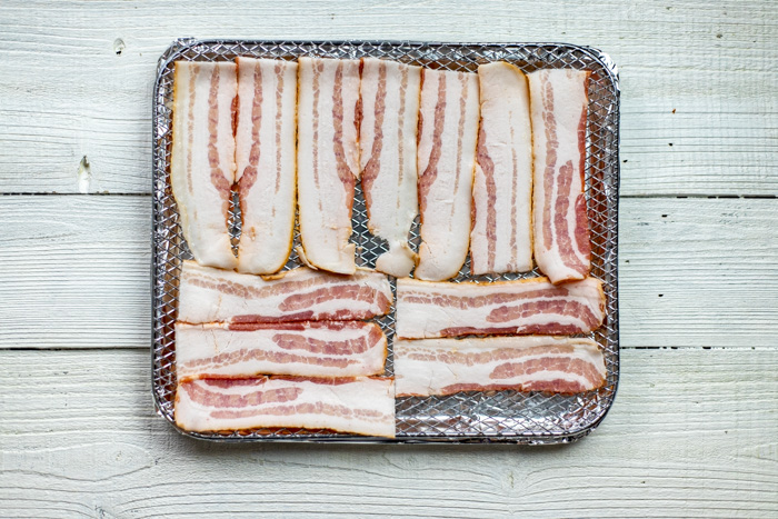 Raw bacon strips on an air fryer tray on a white wooden background