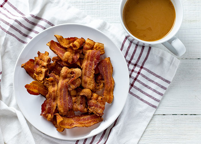 Pile of crispy cooked bacon on a round white plate on a white and red towel next to a white mug of coffee all on a white wooden surface