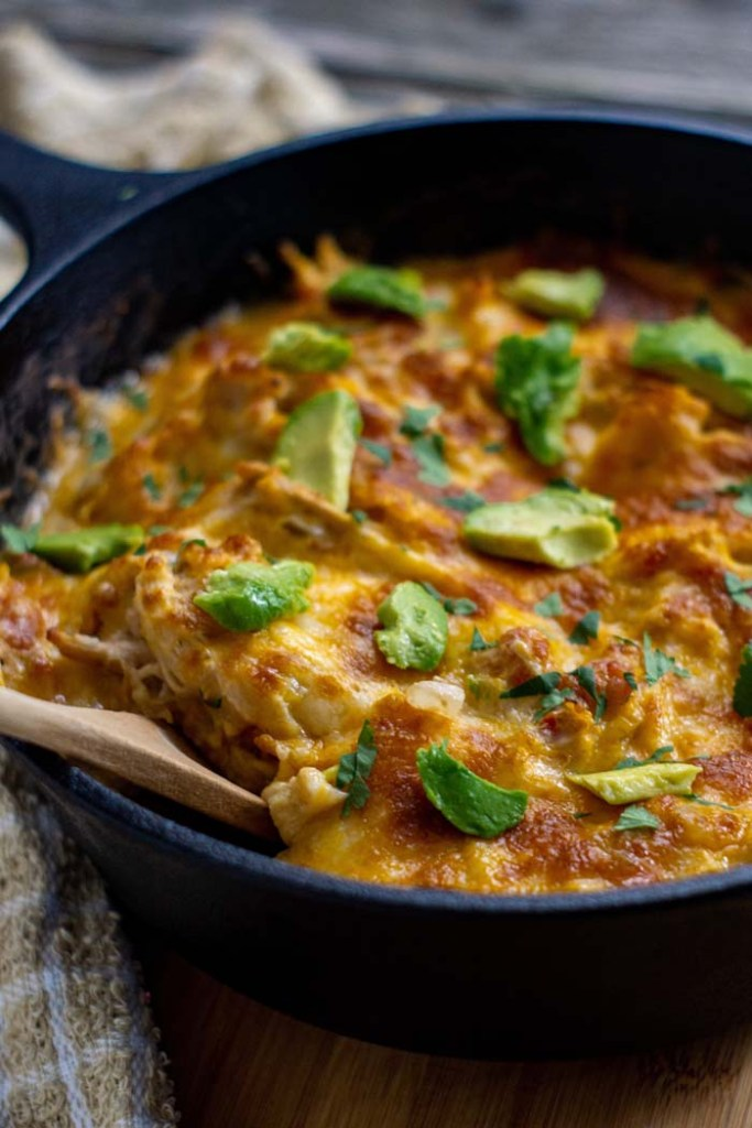 Chicken enchilada suizas topped with sliced avocado and cilantro with a wooden spoon in a cast iron skillet on a wooden surface (vertical)